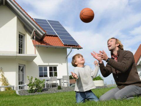 Familie spielt vor Haus mit Photovoltaik