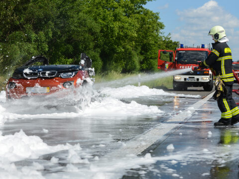Feuerwehr löscht mit Schaum ein brennendes Elektroauto auf der Autobahn